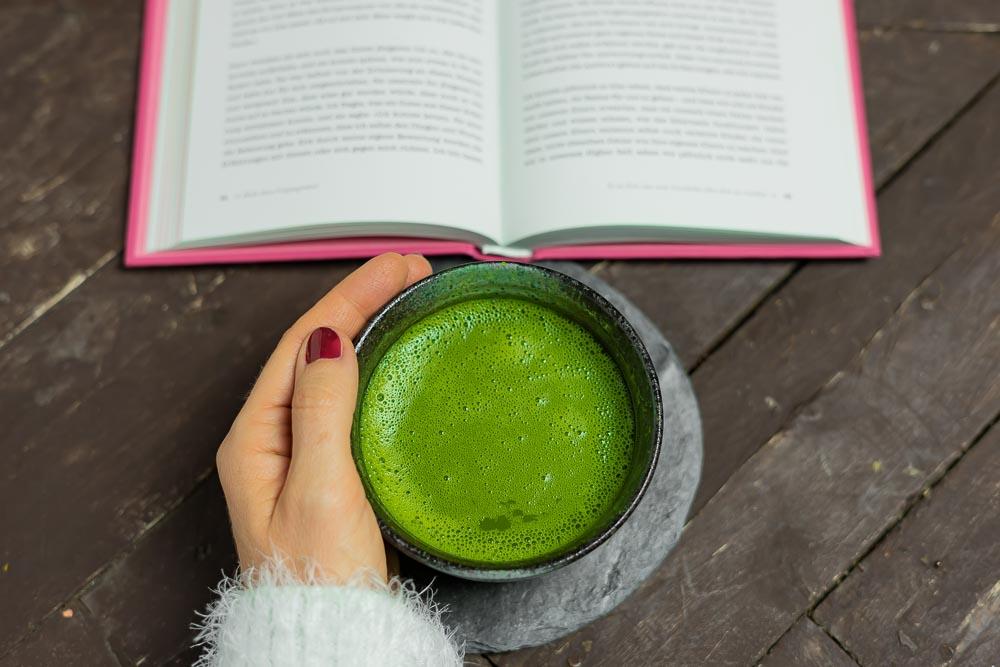 Hand hält Tasse mit Matchatee beim Buch lesen